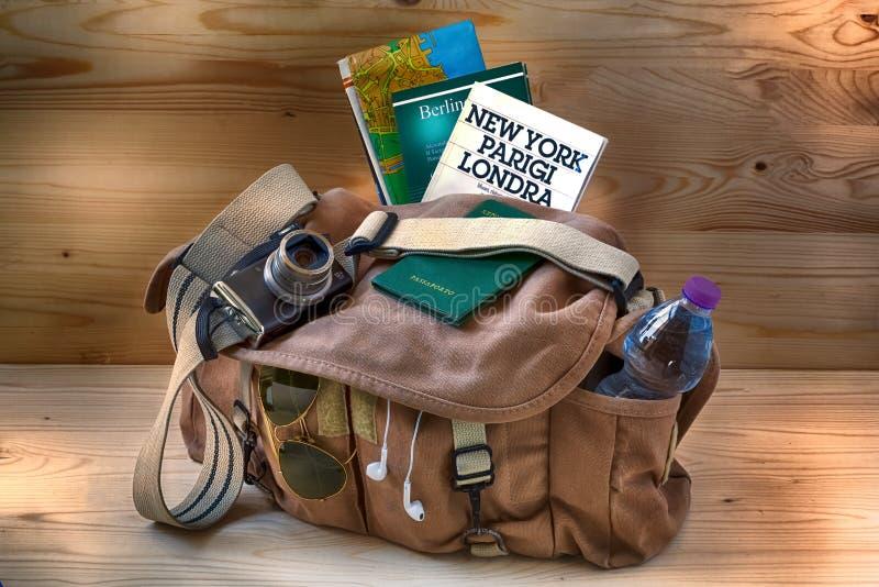 Bolso fotográfico con los mapas, la guía turística y los objetos útiles para el viaje y el turismo libre illustration