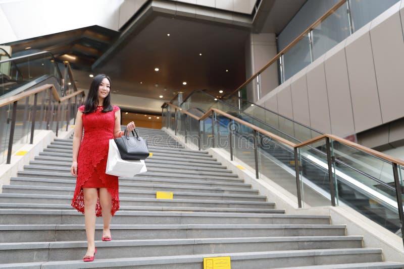 Bolso moderno chino bastante asiático de la tarjeta de las compras de la sonrisa de la muchacha de la mujer de moda en un paseo c imagen de archivo