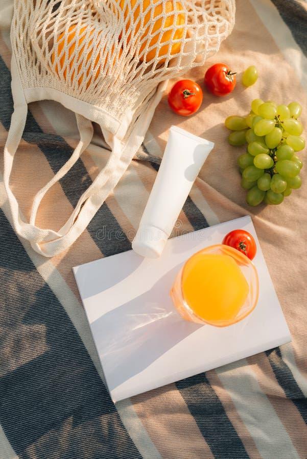 Bolso neto con chancleta, crema de la fruta del sol en la tela escocesa foto de archivo libre de regalías