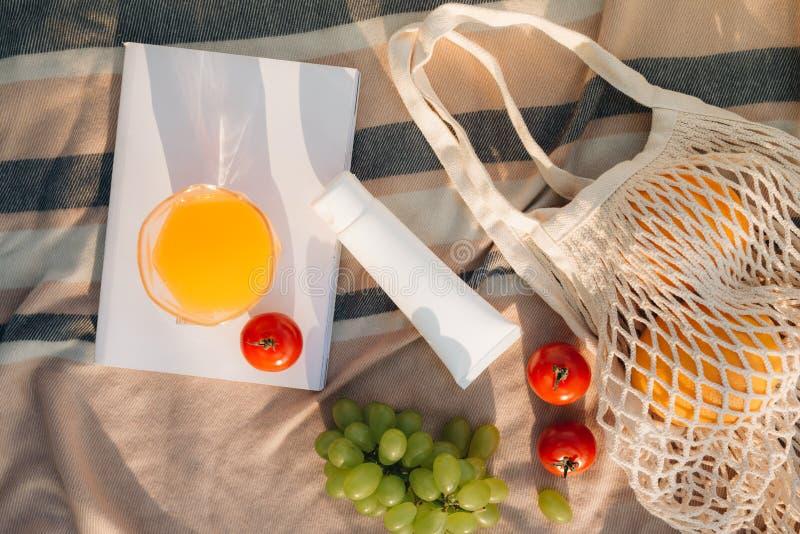 Bolso neto con chancleta, crema de la fruta del sol en la tela escocesa fotos de archivo libres de regalías