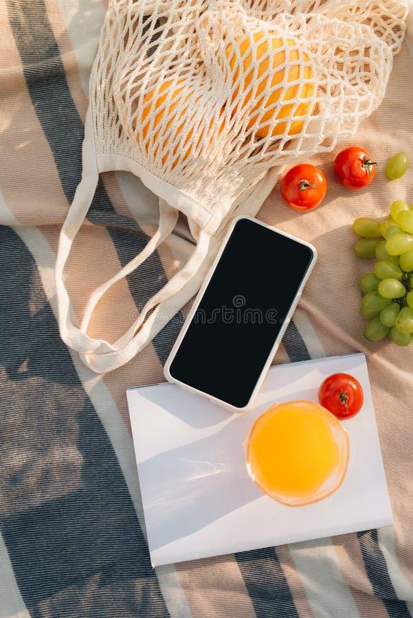 Bolso neto con chancleta, tel?fono, cuaderno de la fruta en la tela escocesa imágenes de archivo libres de regalías
