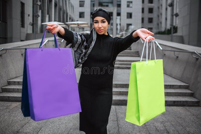 Bolso que hace compras colorido y mirada del control árabe joven confiado de la mujer en la cámara Ella sonríe un pedazo El model foto de archivo libre de regalías