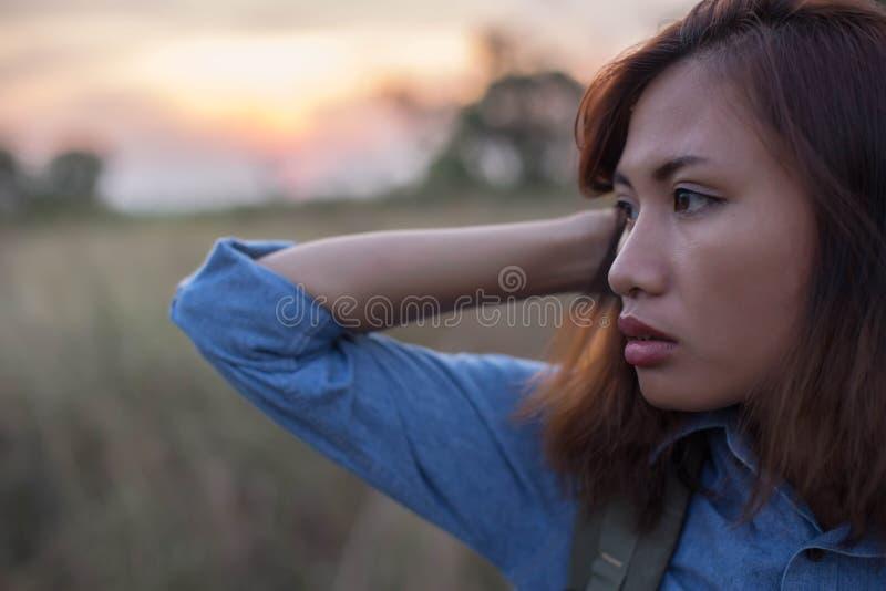 Bolso que lleva de la mujer de viajeros en las puestas del sol del campo foto de archivo