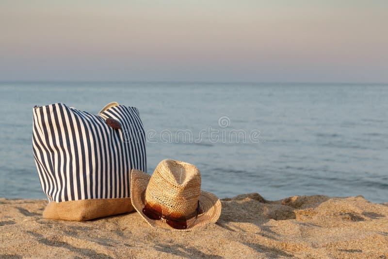 Bolso rayado del verano con el sombrero de paja y las gafas de sol en la playa, fondo del mar tranquilo Tiempo de la puesta del s fotografía de archivo