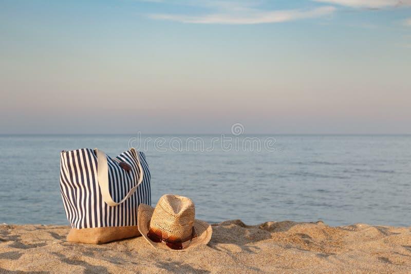 Bolso rayado del verano con el sombrero de paja y las gafas de sol en la playa, fondo del mar tranquilo Tiempo de la puesta del s imagen de archivo libre de regalías
