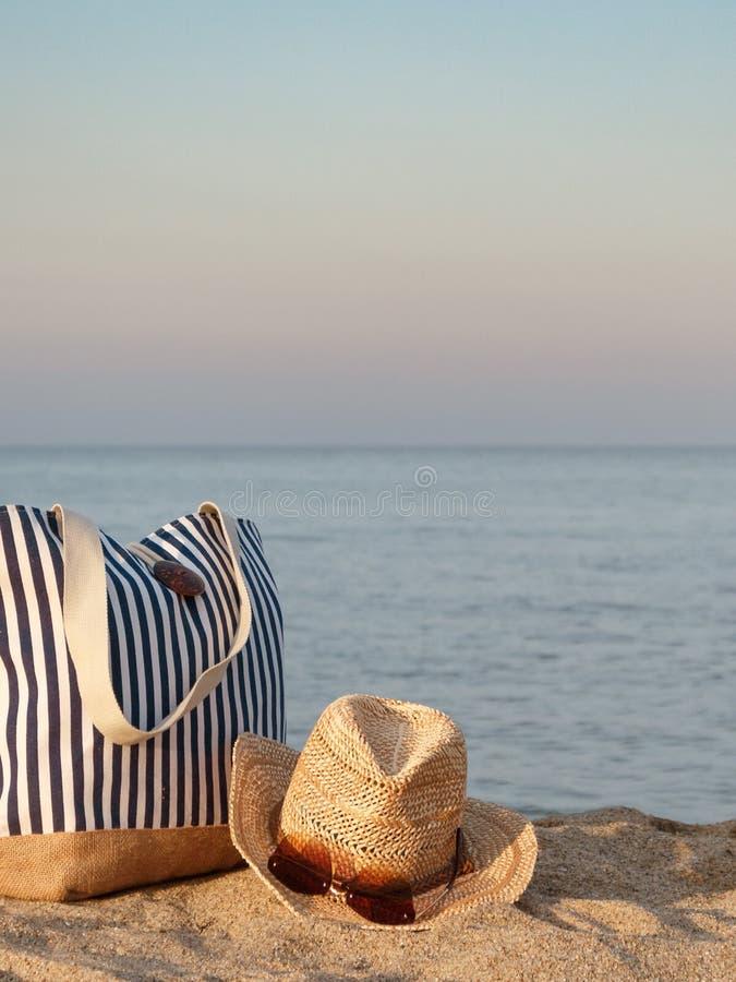 Bolso rayado del verano con el sombrero de paja y el primer de las gafas de sol en la playa, fondo del mar tranquilo Tiempo de la fotos de archivo libres de regalías