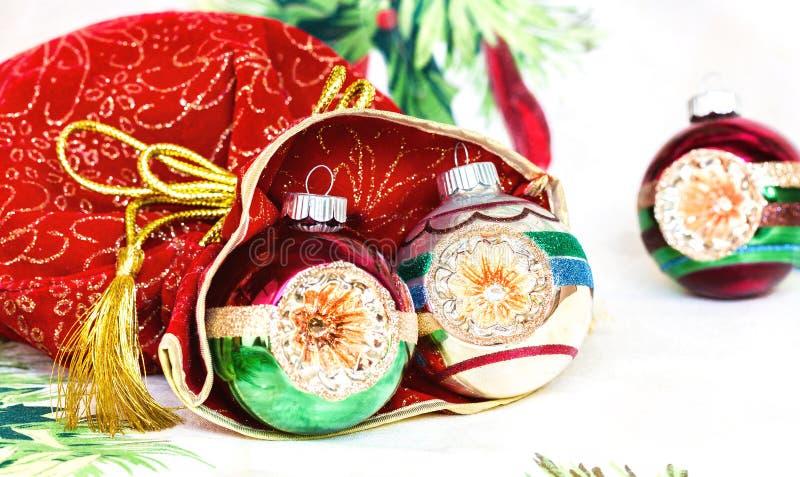 Bolso rojo del ` s del Año Nuevo para los regalos con las bolas de la Navidad en mantel festivo imágenes de archivo libres de regalías