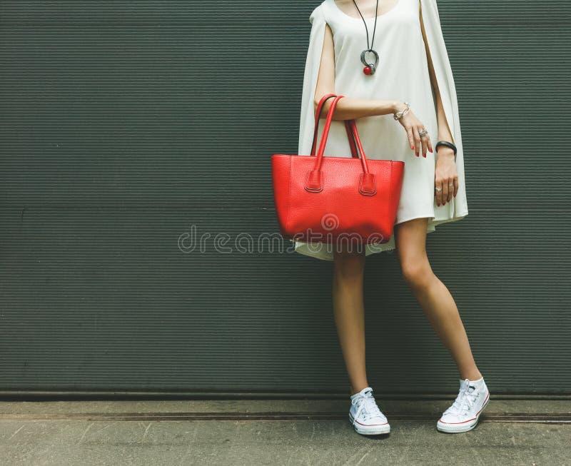 Bolso rojo grande hermoso de moda en el brazo de la muchacha en un vestido blanco de moda, presentando cerca de la pared en a foto de archivo
