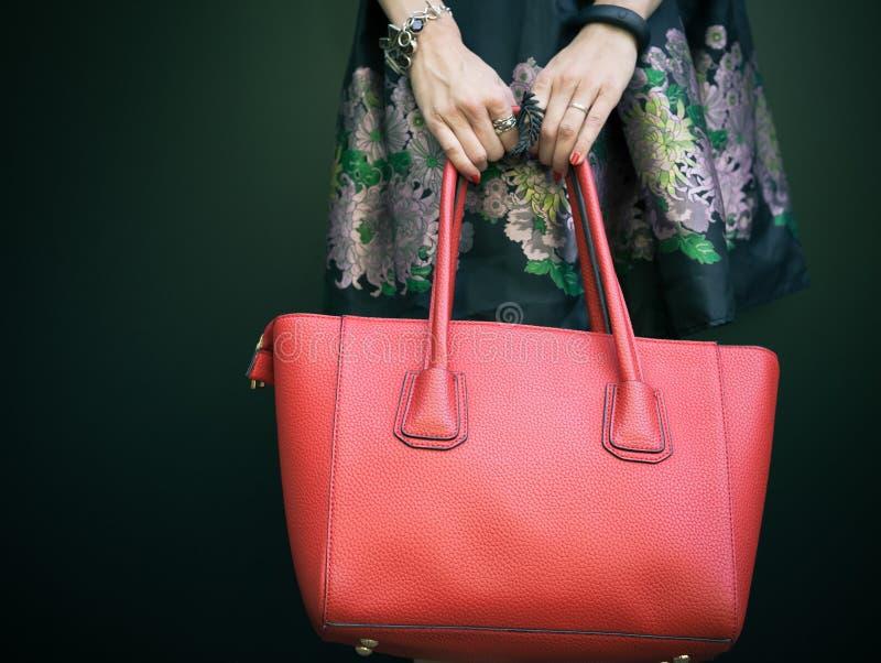 Bolso rojo grande hermoso de moda en el brazo de la muchacha en un vestido negro de moda, presentando cerca de la pared negra en  fotos de archivo libres de regalías