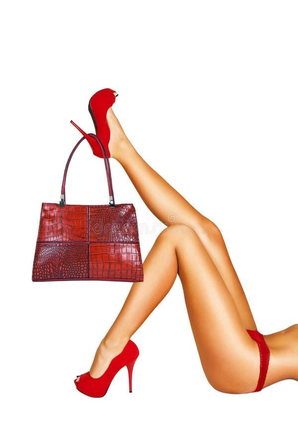 Bolso rojo que cuelga en un zapato de tacón alto. fotografía de archivo libre de regalías
