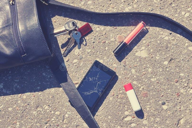 Bolso, teléfono roto, llaves y lápiz labial en la calle del asfalto imagen de archivo libre de regalías