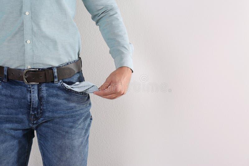 Bolso vazio da exibição do homem no fundo claro, close up imagem de stock