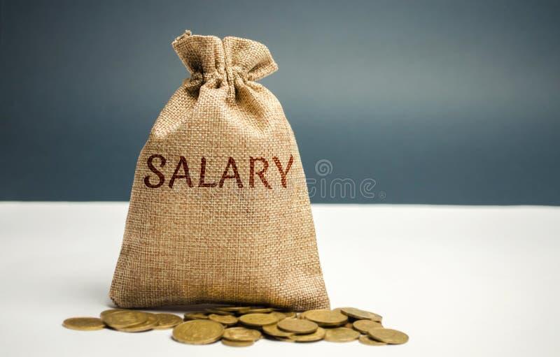 Bolso y monedas del dinero con el sueldo de la palabra El concepto de acumulación de salarios Beneficios y renta de ahorro payrol foto de archivo