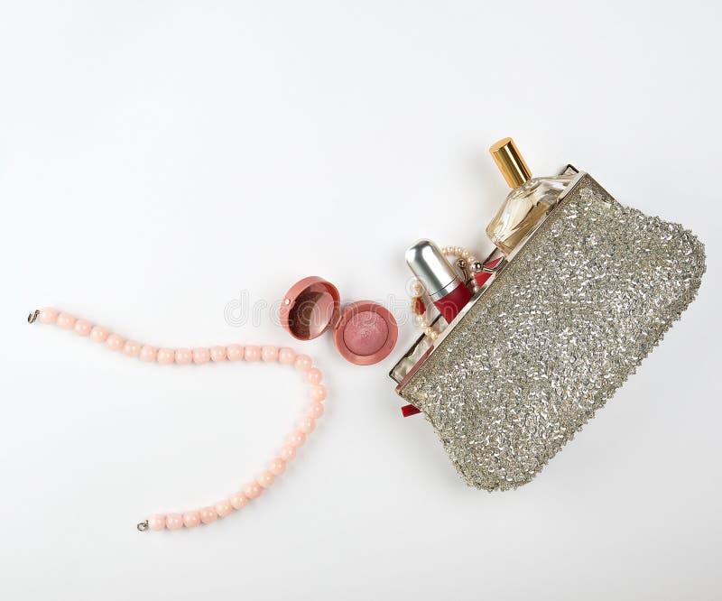 bolso y mujeres cosméticos de plata abiertos \ 'cosméticos y perfumes, barra de labios roja, perfume de s imagenes de archivo