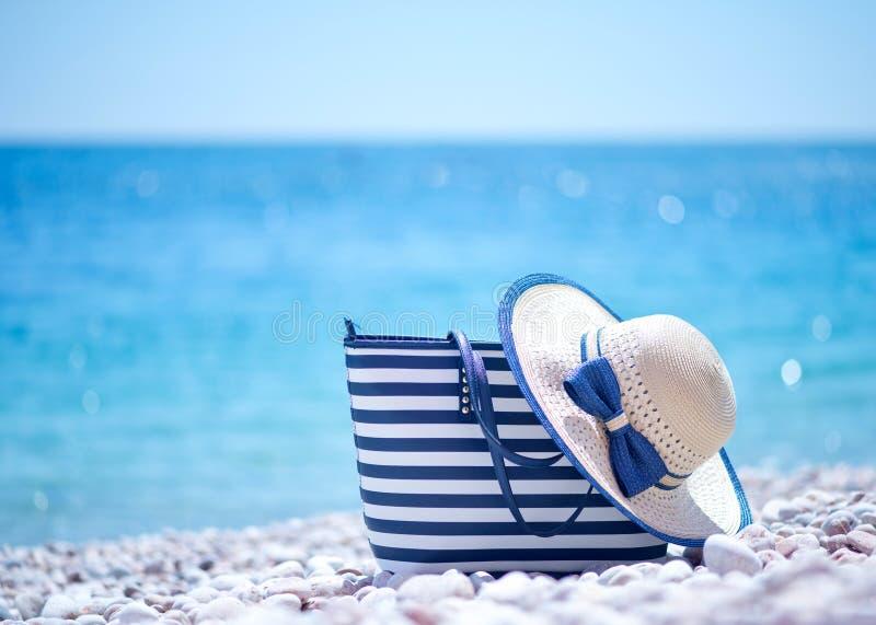 Bolso y sombrero en la playa imágenes de archivo libres de regalías