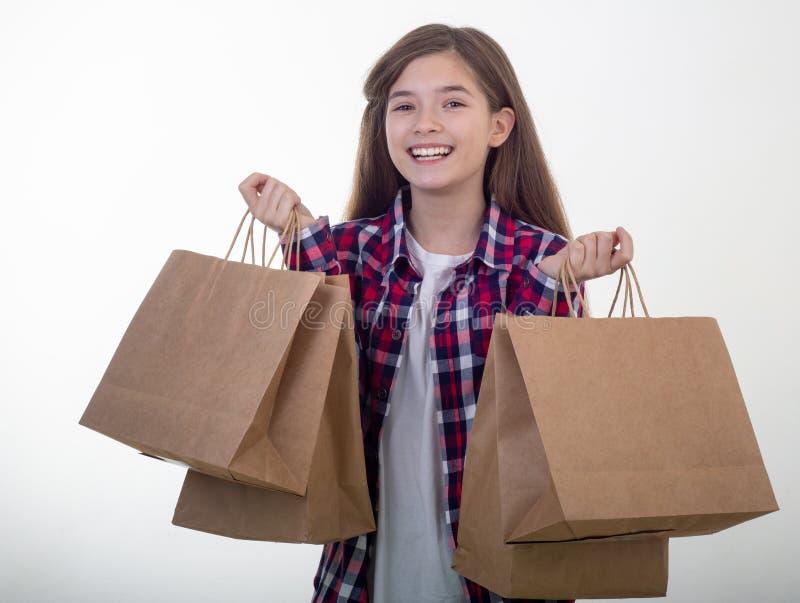 Bolsos blancos de la tarjeta y de compras de la chica joven del descuento feliz de la tenencia en sus manos Niño con la tarjeta d fotografía de archivo libre de regalías
