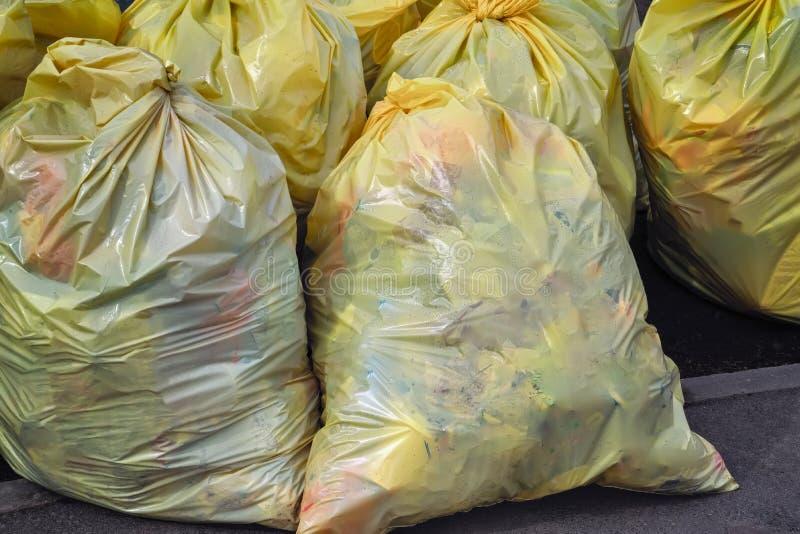 Bolsos de basura plásticos amarillos Basura reciclable que consiste en el vidrio, el plástico, el metal y el papel en el camino l imagen de archivo libre de regalías