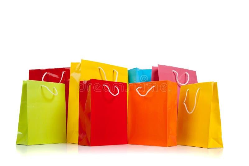 Bolsos de compras coloreados clasificados en blanco imagenes de archivo