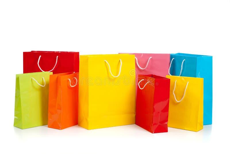 Bolsos de compras coloreados clasificados en blanco fotografía de archivo libre de regalías