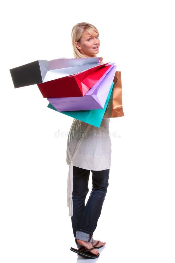 Bolsos de compras de la mujer que llevan rubia fotografía de archivo libre de regalías