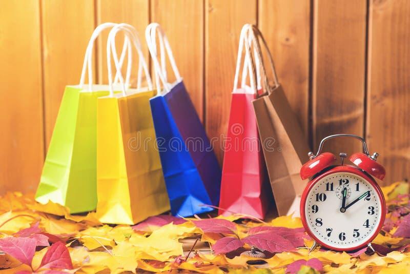 Bolsos de compras del color en fondo caido de las hojas, con el despertador retro Hora para las ventas estacionales Concepto de l foto de archivo libre de regalías