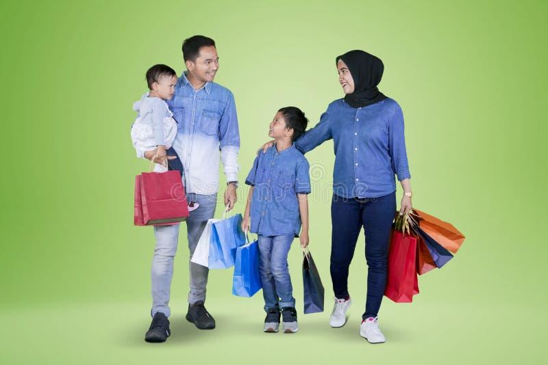 Bolsos de compras de la familia que llevan feliz en estudio foto de archivo libre de regalías