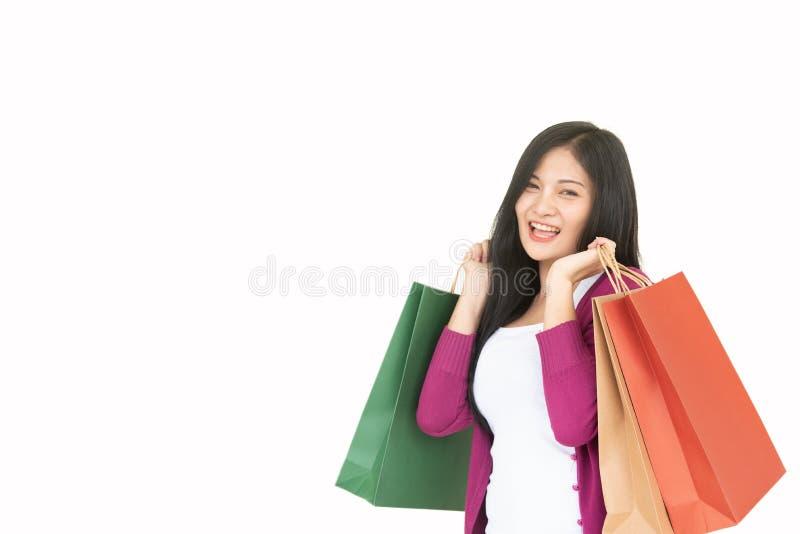 Bolsos de compras de la mujer hermosa de la mujer que llevan que hacen compras hermosa asiática en un fondo blanco imágenes de archivo libres de regalías
