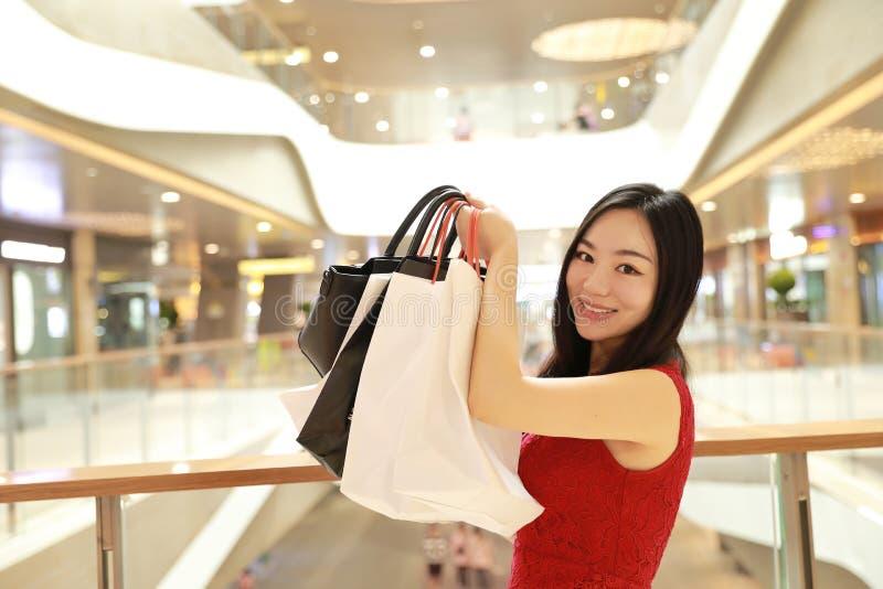 Bolsos de compras modernos chinos asiáticos felices de la mujer de moda en un consumo casual de la risa de la sonrisa del comprad foto de archivo
