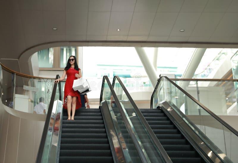 Bolsos de compras modernos chinos asiáticos felices de la mujer de moda en una elevación casual del elevador de la risa de la son fotografía de archivo