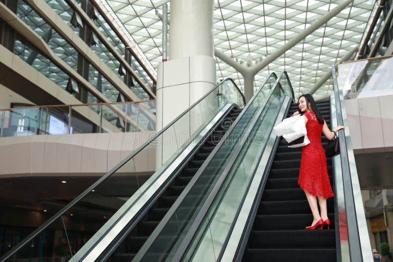 Bolsos de compras modernos chinos asiáticos felices de la mujer de moda en una elevación casual del elevador de la risa de la son foto de archivo libre de regalías