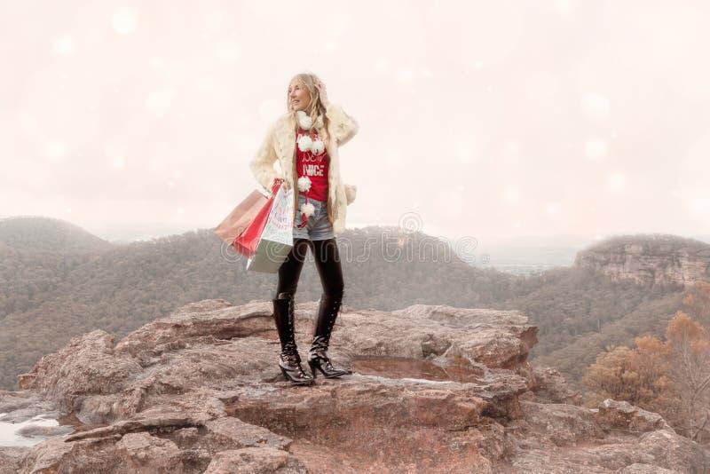 Bolsos de compras que se sostienen femeninos una Navidad hivernal de la escena en las montañas fotos de archivo libres de regalías