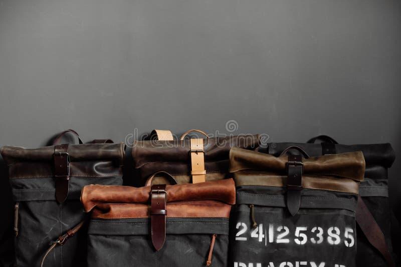 Bolsos de cuero cerca de la pared gris en el cuarto imagenes de archivo