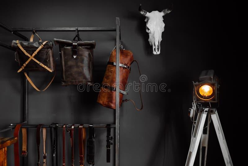 Bolsos de cuero y correas de cuero cerca de la pared fotos de archivo libres de regalías