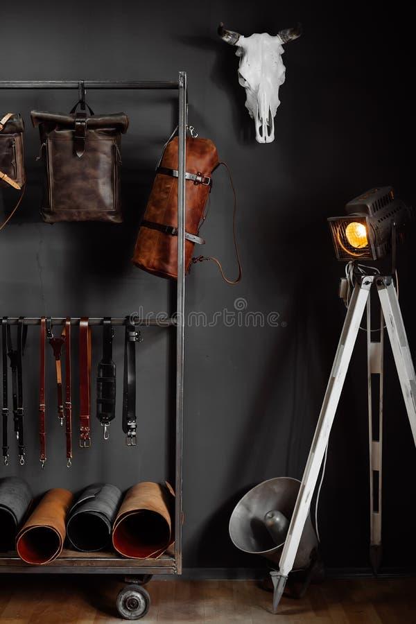 Bolsos de cuero y correas de cuero cerca de la pared imágenes de archivo libres de regalías