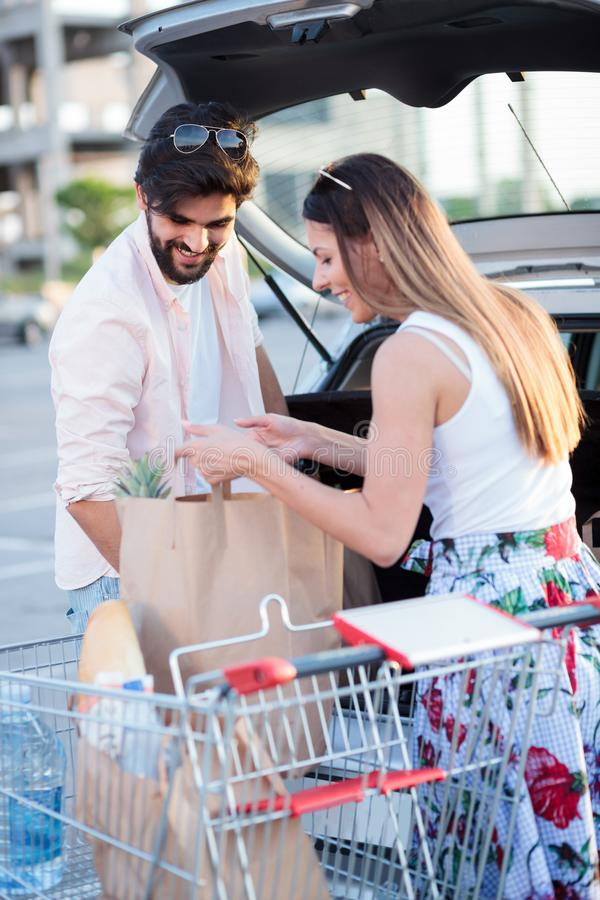 Bolsos de ultramarinos cargados de los pares jovenes felices en un coche imagen de archivo libre de regalías