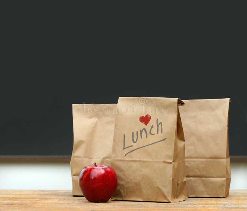 Bolsos del almuerzo con la manzana en el escritorio de la escuela fotografía de archivo