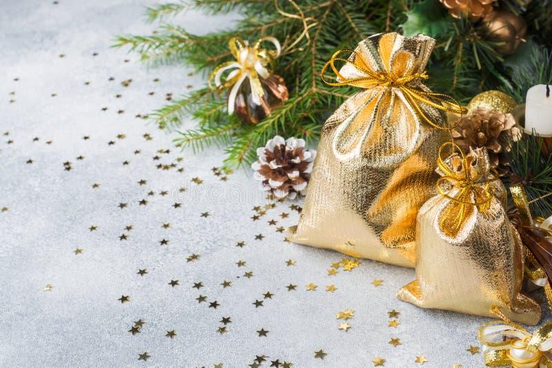 Bolsos del oro con los regalos de la Navidad en el fondo de árboles de navidad y del fondo gris de las decoraciones Concepto de l foto de archivo libre de regalías
