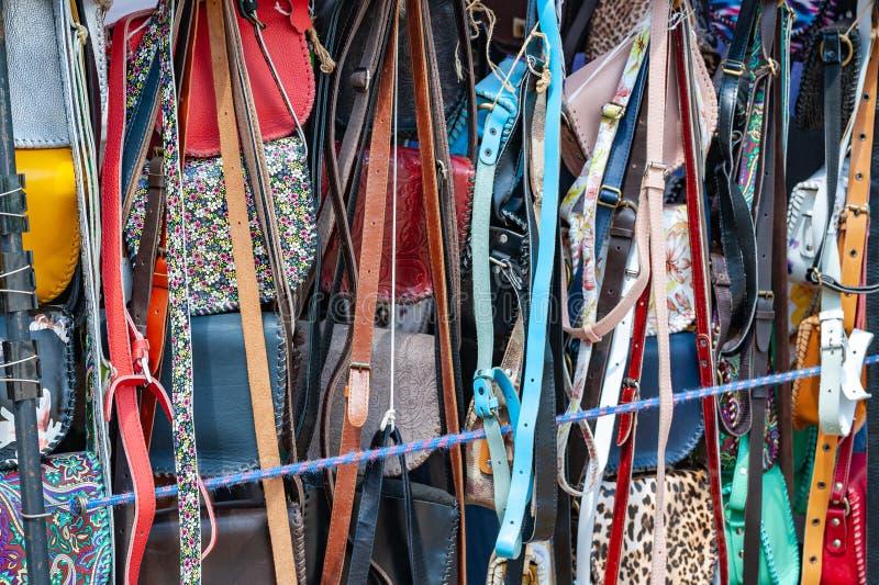Bolsos multicolores y correas hechos a mano en la ventana de un vendedor ambulante fotos de archivo libres de regalías