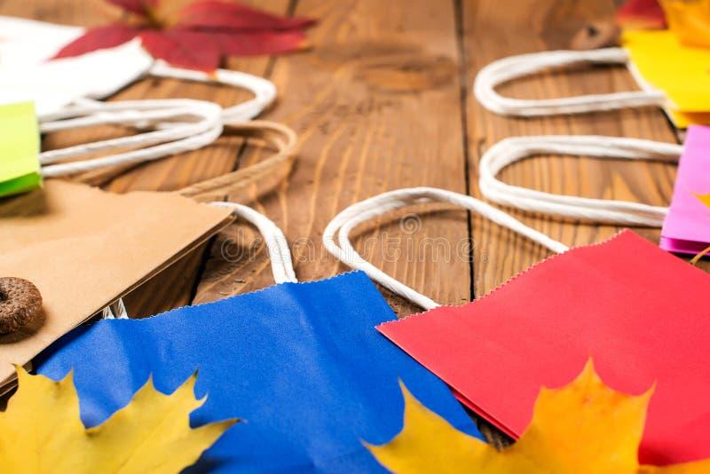 Bolsos que hacen compras y hojas de otoño coloridos en la tabla de madera Ventas del otoño Compras en tiempo del otoño imágenes de archivo libres de regalías