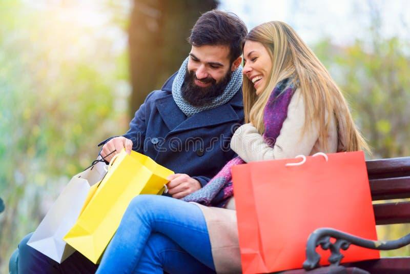 Bolsos que llevan de los pares cariñosos jovenes hermosos y goce junto el hacer compras foto de archivo libre de regalías