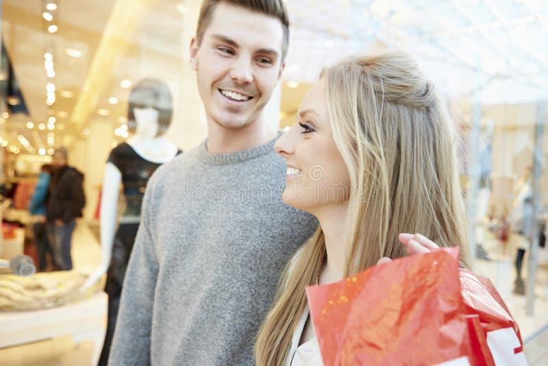 Bolsos que llevan de los pares felices en alameda de compras imagen de archivo libre de regalías