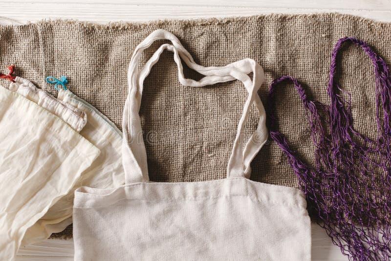 Bolsos reutilizables naturales de Eco para hacer compras, endecha plana en backg rústico foto de archivo