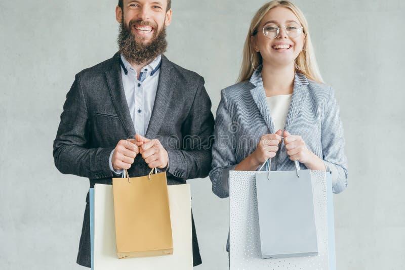 Bolsos sonrientes felices de los pares de la afición de las compras de la familia imágenes de archivo libres de regalías