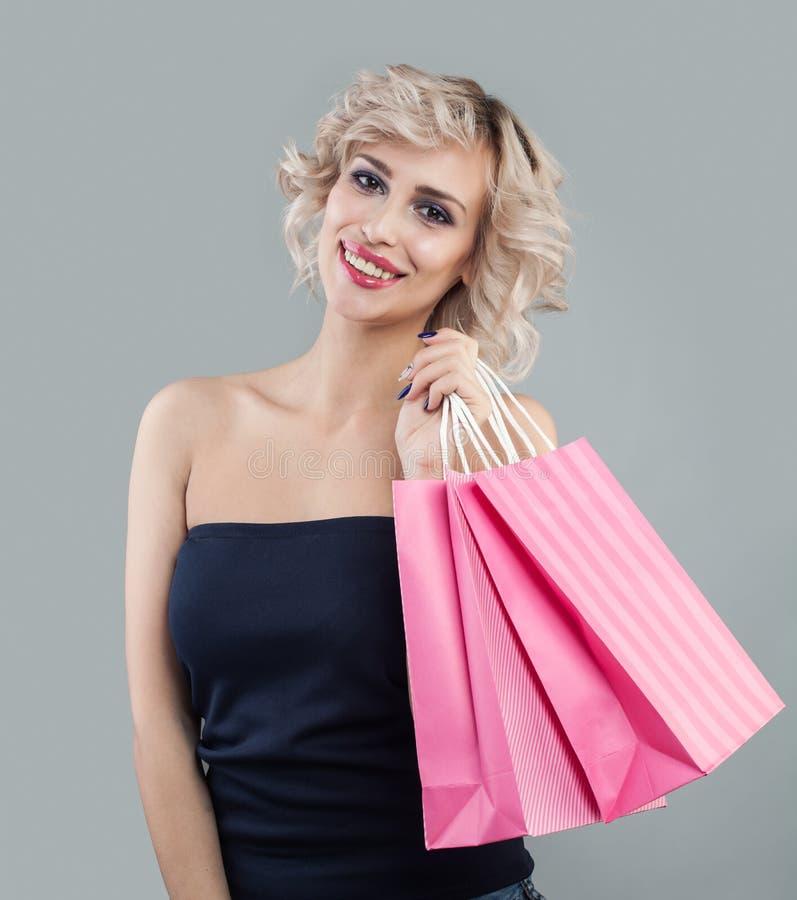 Bolsos y sonrisa de compras de la explotaci?n agr?cola de la mujer fotos de archivo libres de regalías