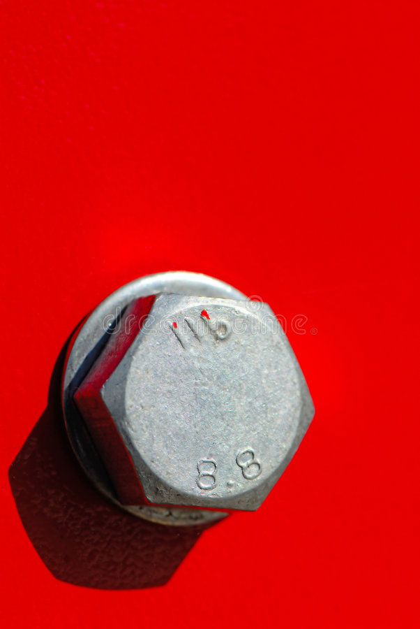 Bolt. Silvery color bolt on red background, close up stock image