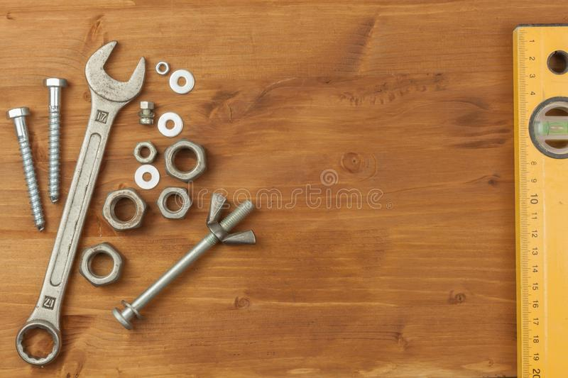 Bolt and nut on a wooden background. Mounting spanner. Background with working tools. Workshop equipment. Buyers repairman royalty free stock photo