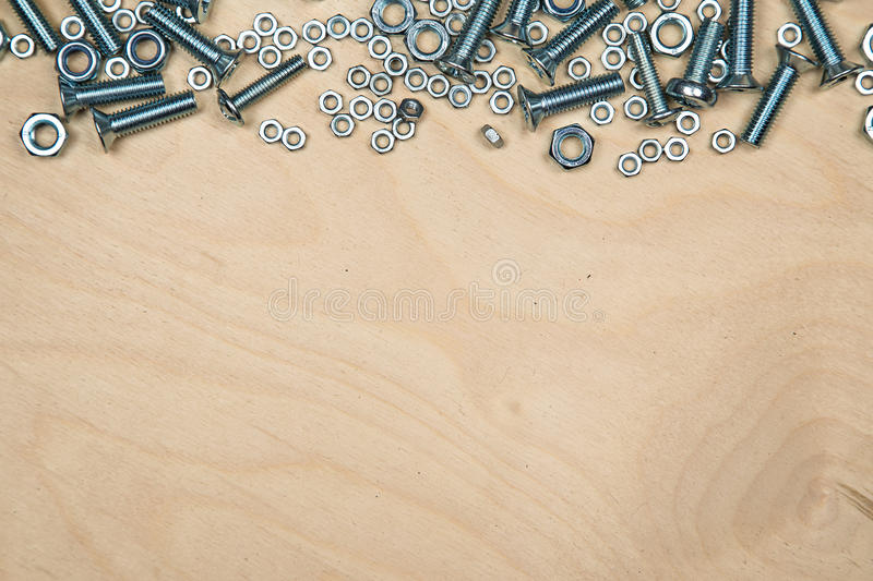 Boltas and nuts on top with wood background royalty free stock image