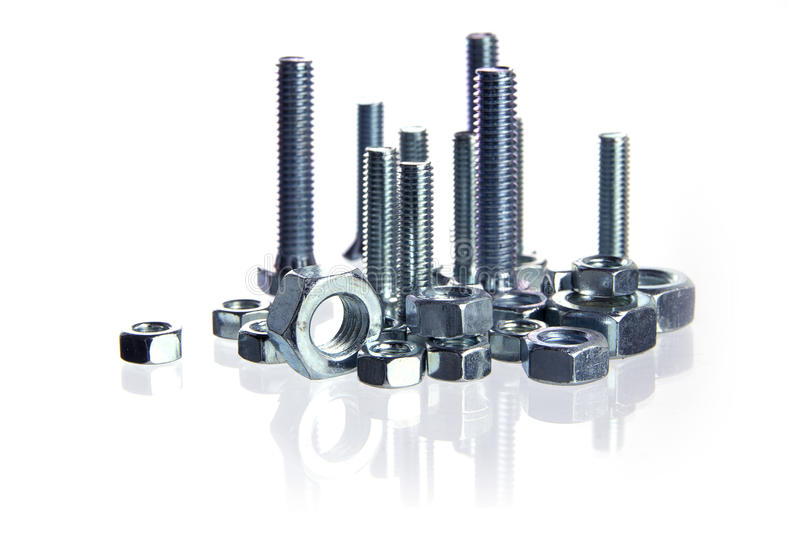 Bolts and nuts standing like a skyline isolated with reflections. On a white background, business concept for construction, crafts and industry, selected focus stock photo