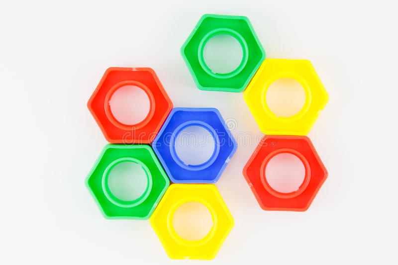 Bolts and nuts toy. Colorful plastic toy, bolts and nuts on a white background royalty free stock photos