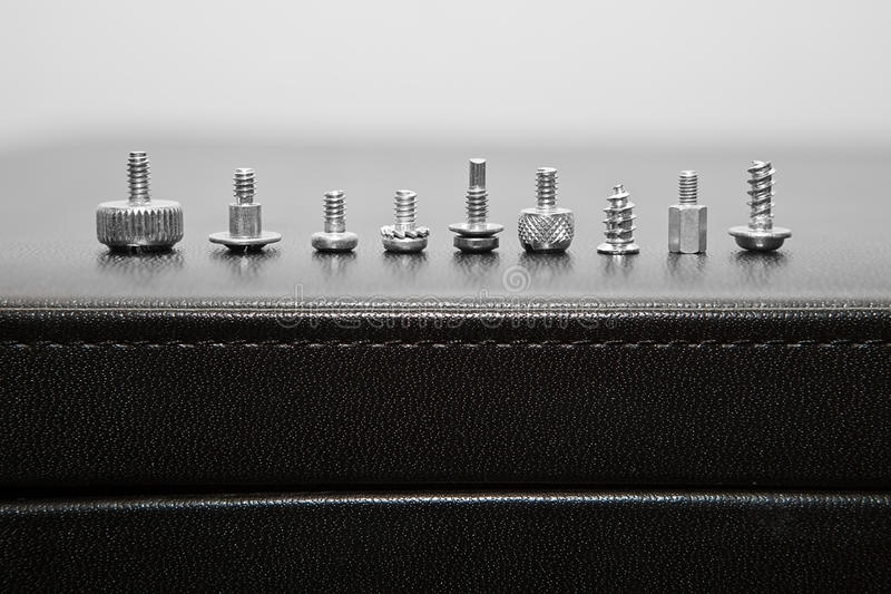 Bolts and screws. On a leather surface royalty free stock photos
